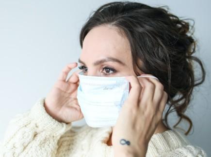 Nainen laittamassa maskia kasvoille