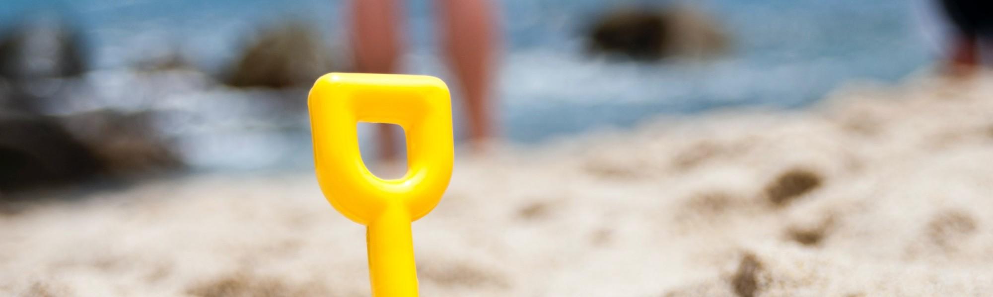 Kuvassa on keltainen muovilapio pystyssä rantahiekassa.