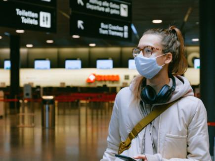 Nuori nainen lentokentällä maski kasvoilla ja kuulokkeet kaulalla