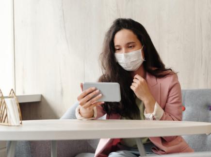 Nainen istuu kahvilassa ja katsoo mobiililaitetta