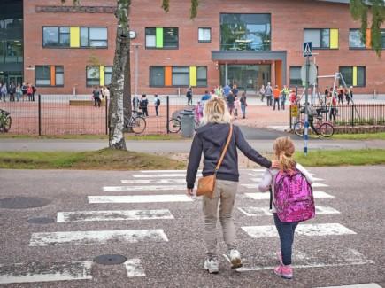 Ekaluokkalainen ylittämässä suojatietä kouluun saattajan kanssa.