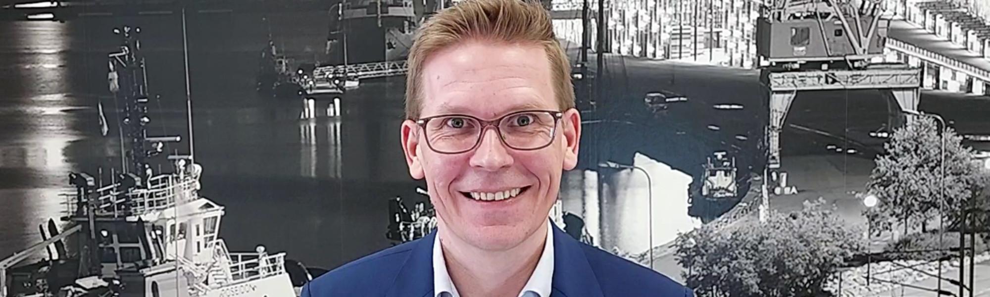 Kuvassa Sami Virtanen. Taustalla mustavalkoinen kuva Kotkan Kantasatamasta.