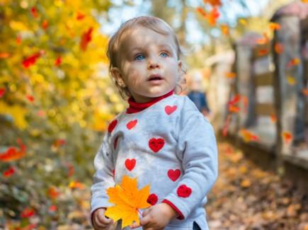 Kuvassa on pieni tyttö, jolla on siniset silmät ja sydänkuvioitu paita. Taustalla näkyy syksyinen luono ja ruskan värjäämiä lehtiä. Tyttö pitää kädessään keltaista vaahteranlehteä.