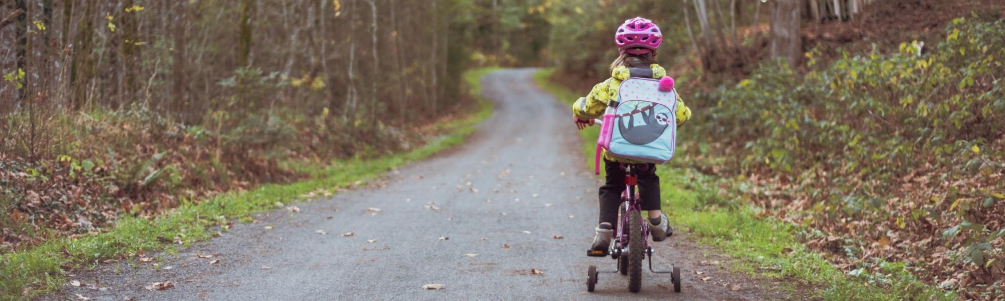Kuvassa on pieni tyttö takaa kuvattuna ja hän ajaa apupyörillä varustettua polkupyötää reppu selässä. Maisema on syksyinen.