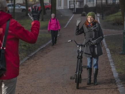 Nainen taluttaa pyörää ja tervehtii vastaantulijaa kädellä