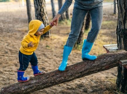 Kuvassa aikuinen pitää kädestä kiinni pientä lasta. Molemmat tasapainoilevat kaltevalla puunrungolla. Maisema on syksyinen.