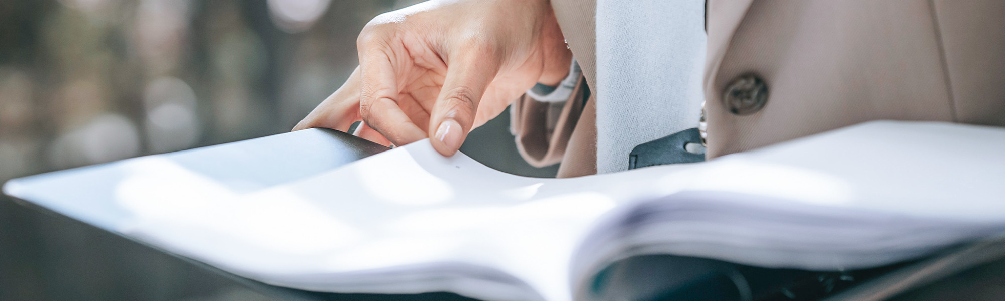 Kuvassa nainen selaa asiakirjakansiota